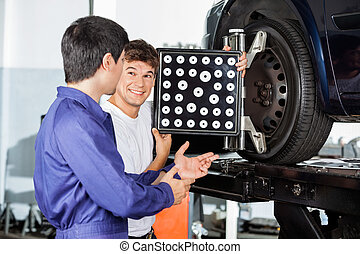 Mechanic With Colleague While Using Wheel Aligner