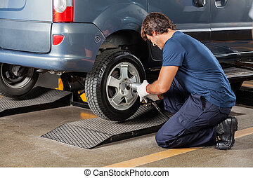 Mechanic Fixing Car Tire At Auto Repair Shop - Side view of...