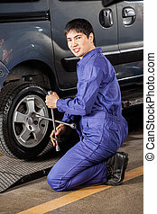 Confident Mechanic Fixing Car Tire At Garage - Side view...