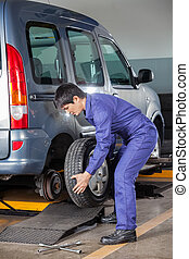 Technician Replacing Car Tire - Young male technician...