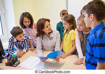 group of school kids with teacher in classroom