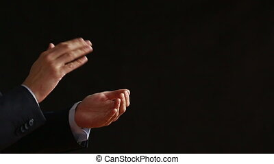 Clapping hands on black background. business suit