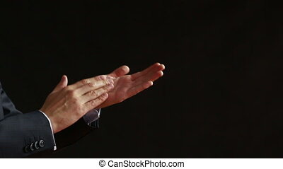 Clapping hands on black background business suit