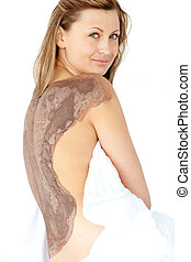 Attractive woman enjoying a mud skin treatment in a Spa...