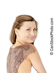 Portrait of a charming woman enjoying a mud skin treatment...