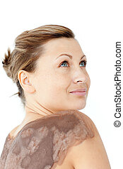 Portrait of a pensive woman enjoying a mud skin treatment in...