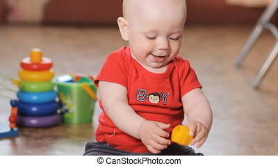 Adorable little boy playing with little toy, smiling.
