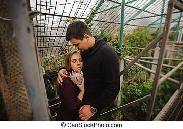 Young couple in greenhouse not looking in camera