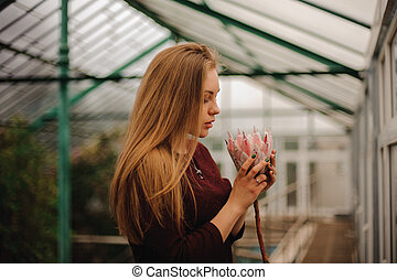 woman smelling pink flower with eyes closed - Attractive...