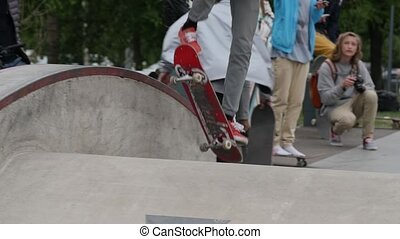 A young man in red shoes doing boardslide trick on a ledge in a skate park