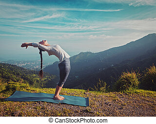 Woman doing yoga Sun salutation Surya Namaskar outdoors -...