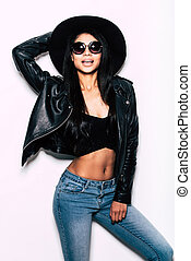 Stylish beauty. Beautiful young mixed race woman in leather jacket and hat posing against white background