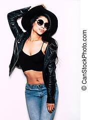 Carefree beauty. Beautiful young mixed race woman in leather jacket and hat posing against white background
