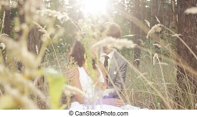 Beautiful couple at sunset Sitting in the tall grass and...