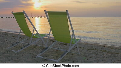 Chaise longues at the seaside at sunset - Two empty chaise...