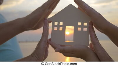 Hands Holding House Silhouette against Sun - Closeup shot of...