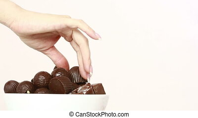 people take chocolates from the plate. binge eating concept....
