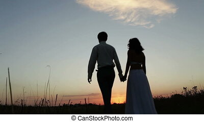Bride and groom go into the sunset - The bride and groom go...