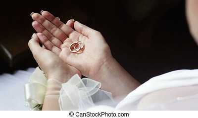 Bride shows wedding rings to the groom