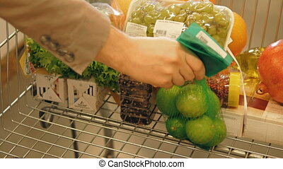 Male Hand Putting Fruit And Alcohol In A Shopping Trolley,...