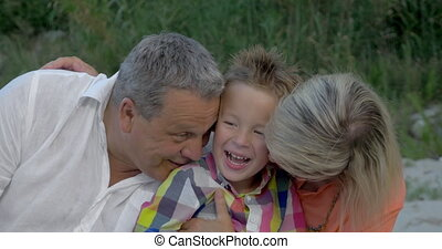 Grandparents Hugging and Kissing Their Grandson - Little boy...