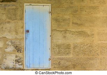 Weathered wooden door with blue paint chipped and peeling.