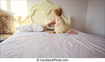 Little Girl Plays Puts Pillows onto White Bed from Floor -...