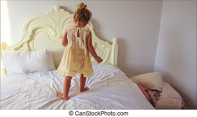 Little Girl Claps Hands Jumps down Bed to Pillows on Floor -...