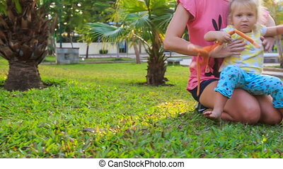 Blond Mother Daughter Squat on Grass among Palms in Park -...