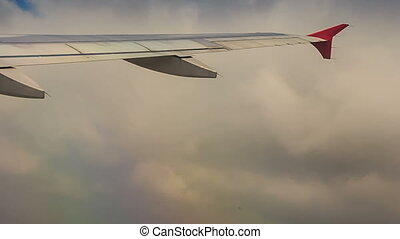 airliner wing cuts white clouds in blue sky while ascending...