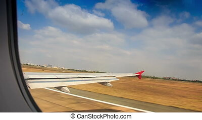 Airliner Landing along Runway out of Window - view of...