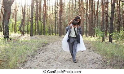 Groom carries his bride - The groom carries his bride on his...