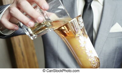 Groom pours champagne - A groom pours champagne Pours from...