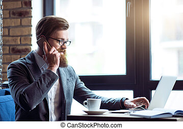 Positive  bearded man talking on cell phone
