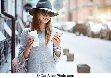 Modern young woman in a big city - Messaging Cheerful and...