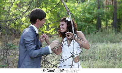Love games newlyweds. The groom breaks a branch, and prevent...