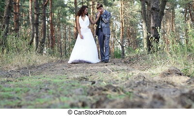 Married couple in pine forest - A young married couple are...