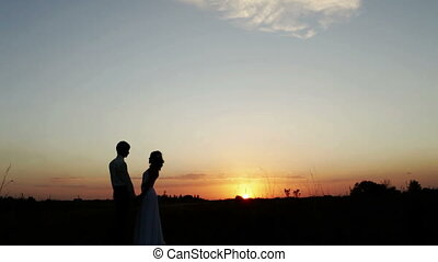 Newlyweds go into the sunset. Stop kissing and then go