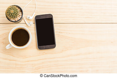 Coffee cup and smartphone on wooden table with copy space...