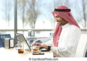 Arab saudi man working online with a laptop and smartwatch...