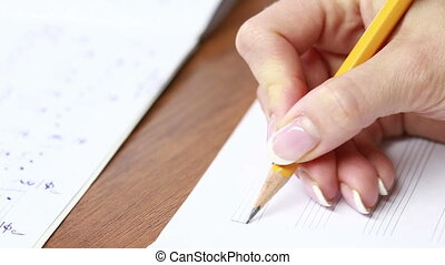 Hand with pencil and music sheet composer writes music -...