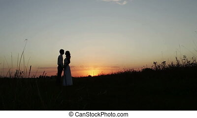 Silhouettes of lovers at sunset Couple in love long kisses...