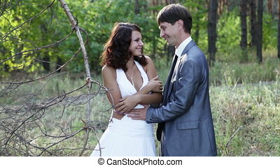 Young married couple in a pine forest. Guys gently touch...