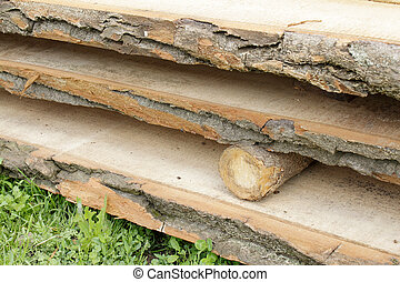 Board lumber lying in stack on the grass