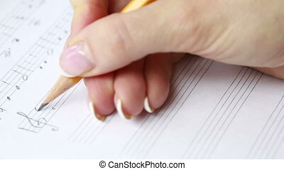 Hand with pencil and music sheet. composer writes music