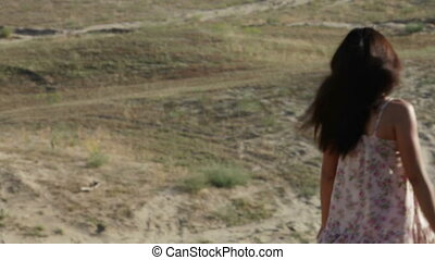 Girl hurries downward on a sandy mountain - Girl, looking...