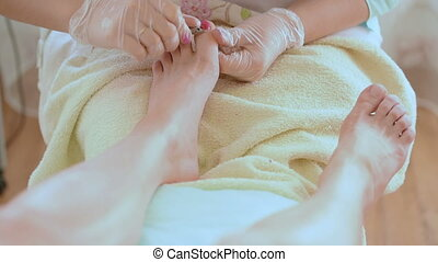 Pedicure nail technician worker perfoming procedure for foot...