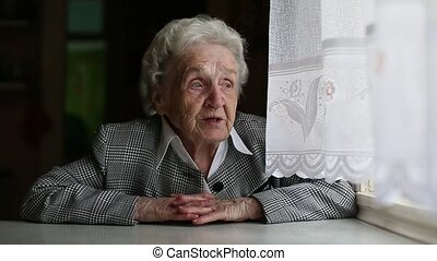 Elderly woman sings/says sitting at the table near the...