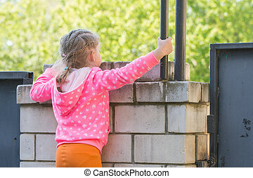 Five-year girl climbed on a brick fence and looks for him
