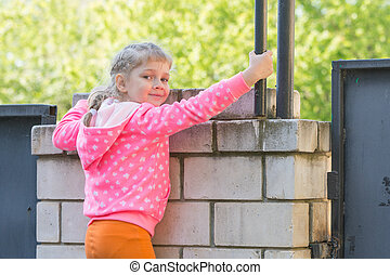 Five-year girl climbed on a brick fence and turned around...